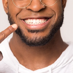 Man pointing to improved smile after ClearCorrect Treatment