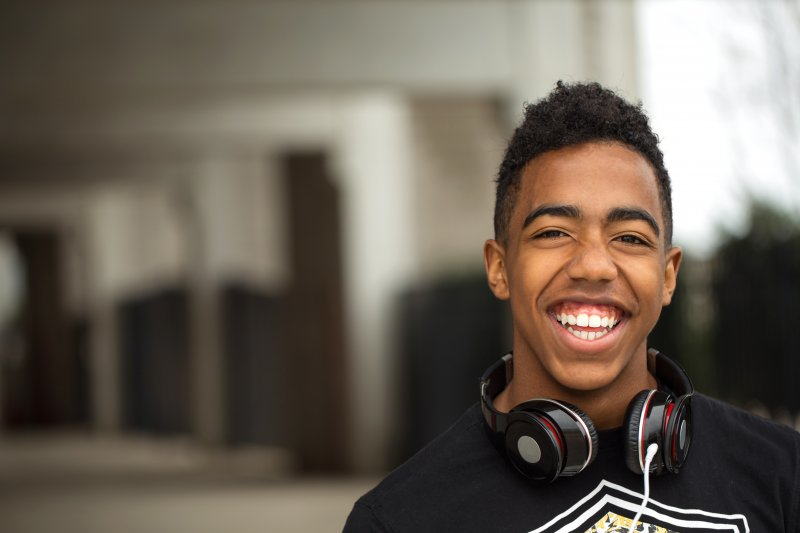 Teenager with headphones smiling and showing all teeth
