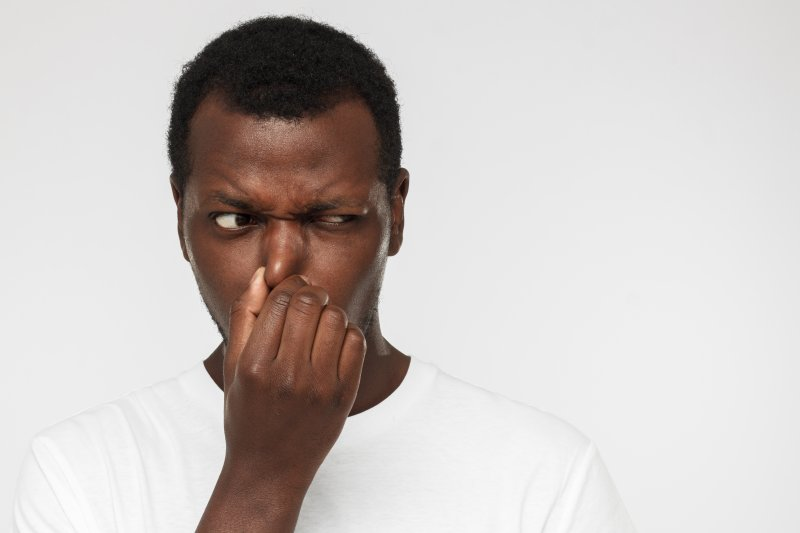 Man covering mouth and nose due to bad breath