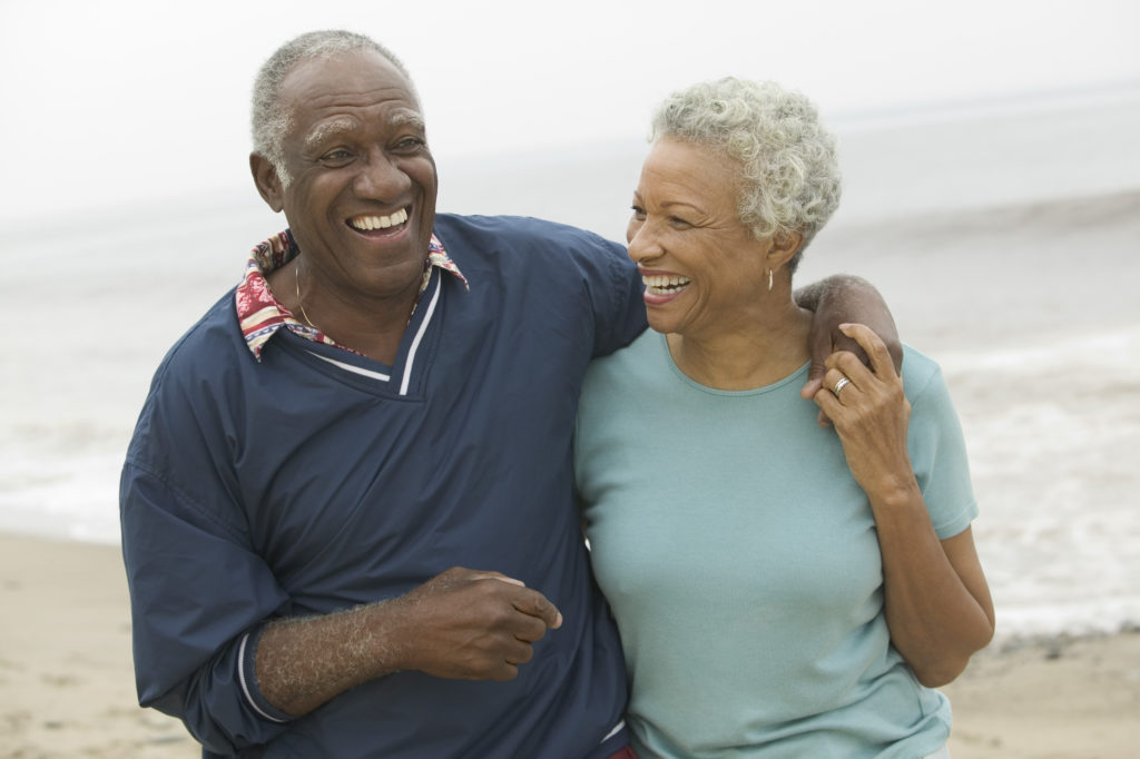 Older couple on the beach smiling and showing teeth