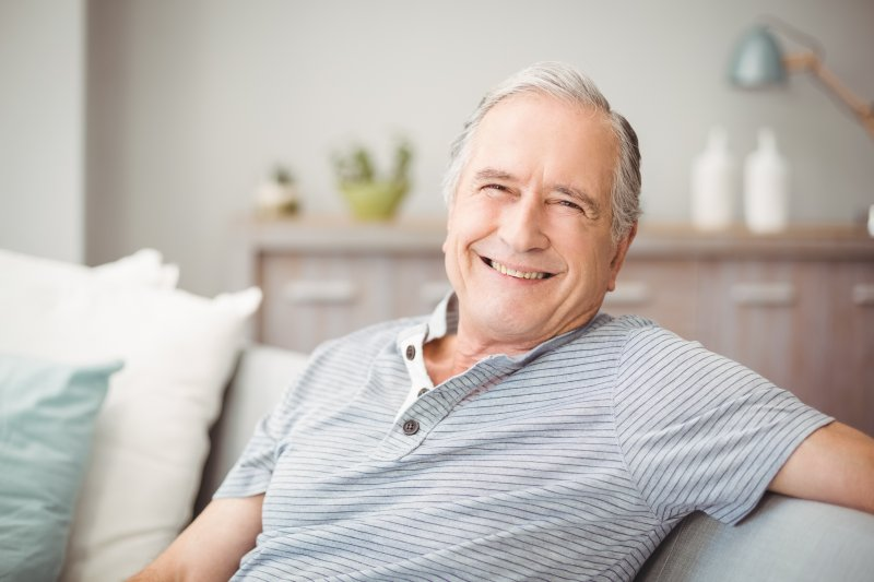 Older man sitting on the couch and smiling