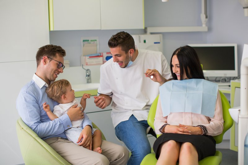 Mother, father, and baby visiting the family dentist