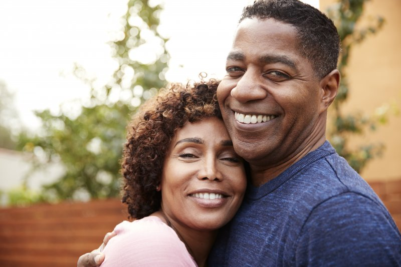 Man and woman with dental implants hugging and smiling