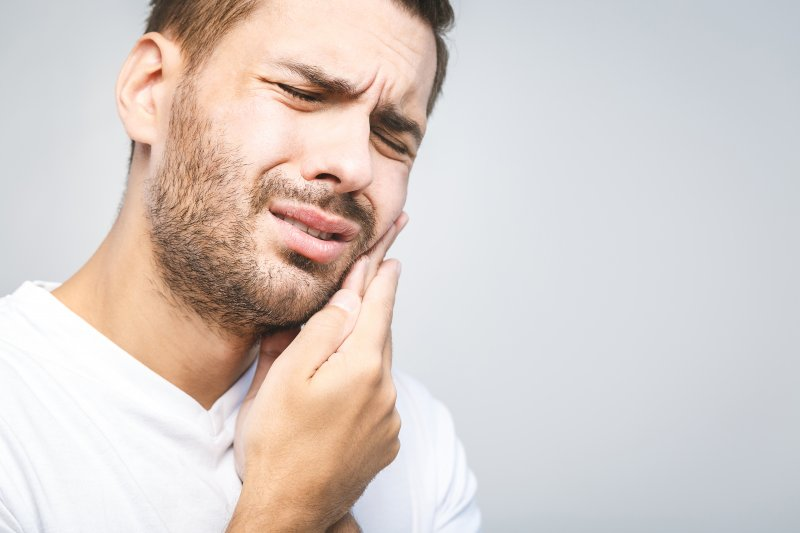 Man in white shirt rubbing his jaw due to toothache