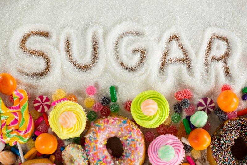 """""""Sugar"""" written in sugar near candy and donuts"""