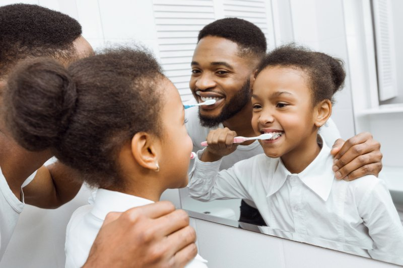 Father helping child brush their teeth in the morning.
